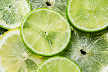Sliced lemon and lime on a dark background, top view, selective