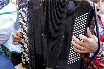 Músico tocando el acordeón en la calle. Músico dando recital en el exterior. Primeros planos de un acordeón.