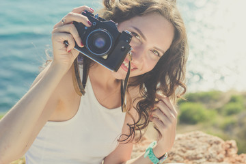 Tourist girl making photo by old camera on mountain top