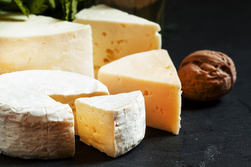 Assorted different kinds of cheese, nuts, herbs, white wine on a