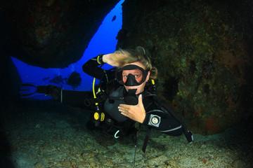 Blonde woman scuba diver having fun and exploring sea caverns