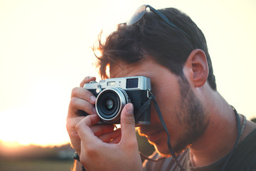 Man shooting with vintage camera at sunset