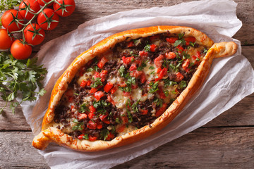 Turkish pide pizza with meat closeup. horizontal view from above