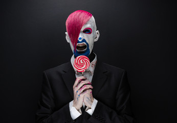 Clown and Halloween theme: Scary clown with pink hair in a black jacket with candy in hand on a dark background in the studio