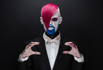 Clown and Halloween theme: Scary clown with pink hair in a black jacket on a dark background in the studio