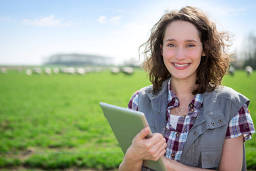 Young attractive farmer in a field using tablet