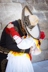 Pareja de novios con traje tradicional mexicano. Pareja besándose. Pareja tapados con sombrero demostrándose amor.