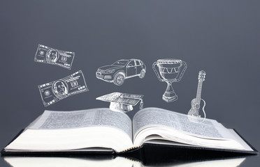 Open book with drawings on grey background