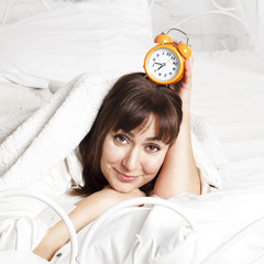 Young beautiful woman in bed with clock