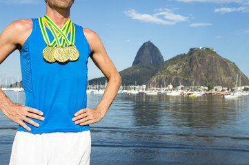 Frst place athlete with three gold medals standing outdoors at Botafogo Bay Rio de Janeiro Brazil