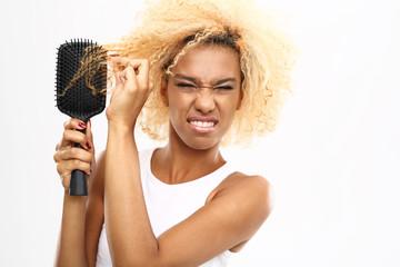 Splątane włosy. Ciemnoskóra młoda kobieta rozczesuje włosy szczotką