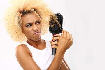 Rozczesywanie włosów. Ciemnoskóra młoda kobieta rozczesuje włosy szczotką