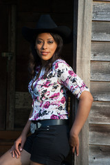 Pretty Hispanic woman outside in Western Hat