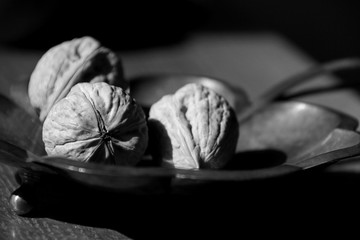 Still-life of the three walnuts laying on a silver decorated plate.Black And White Image