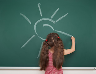 girl drawing sun on school board