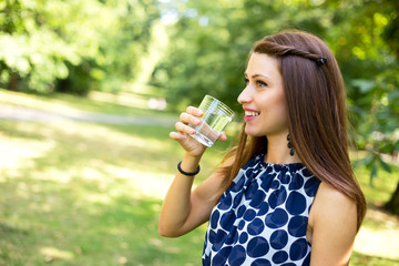 young woman drinking a glass of water outdoors