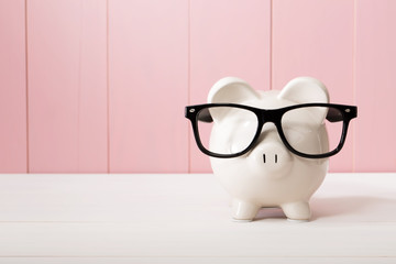 Piggy bank with glasses over pink wooden wall