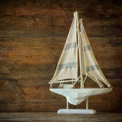old vintage wooden white sailing boat on wooden table