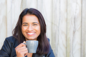 Pretty Indian woman drinking coffee at a cafe