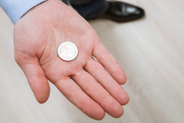 Businessman holding one coin