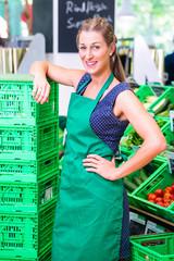 Biomarkt Angestellter füllt in der Gemüseabteilung auf