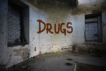 text drugs on the dirty old wall in an abandoned ruined house