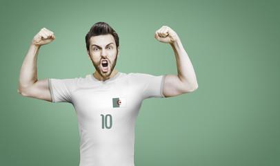 Algerian soccer player celebrates on green background