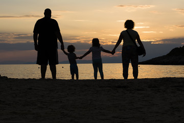 Family on a beach holding hands at sunset