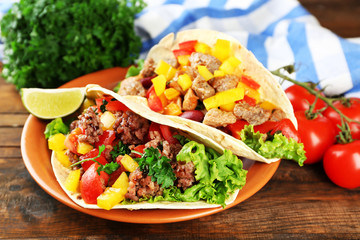 Homemade beef burritos with vegetables on plate, on wooden background
