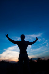 Man on top Conceptual design. Concept of abstract  man with open arms facing a city's silhouette at the sunset