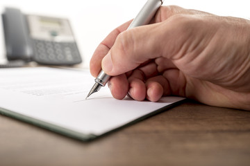 Businessman or lawyer signing important document, legal papers,