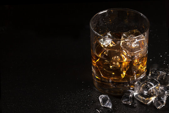 Glass of whiskey with ice on black stone table