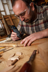 Carpenter carving wood with engraver tool. Restoring the old furniture.