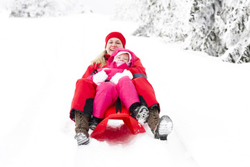 sledding mother and her little daughter