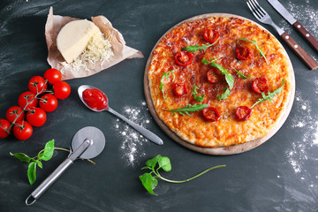 Pizza with arugula and cherry tomatoes on wooden background
