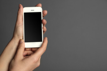 Hands holding mobile smart phone on gray background