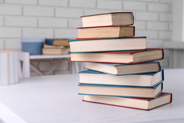 Stack of books on light surface, om bricks wall background