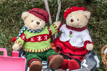display of a couple of second hand teddy bears dressed up for winter or Christmas time with home-made knitwear sold at garage sale for antique collection