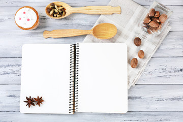 Open recipe book and tasty bakery on wooden background