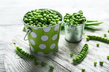 Fresh green peas in metal buckets on white wooden table, closeup