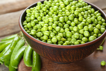 Fresh green peas in clay bowl on wooden cutting board, closeup
