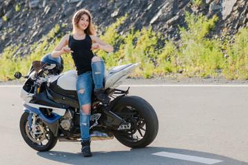 Blonde girl near modern motorcycle.
