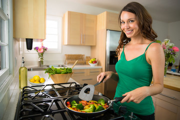 Woman home chef single portrait cooking vegetables vegan meal on stove grill