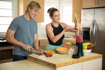 Married couple makes breakfast smoothie at home fruits vegetables in kitchen