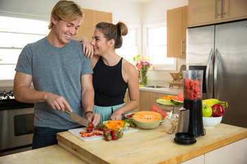 Young handsome beauty couple lovers dating make smoothie slicing fresh fruits and veggies