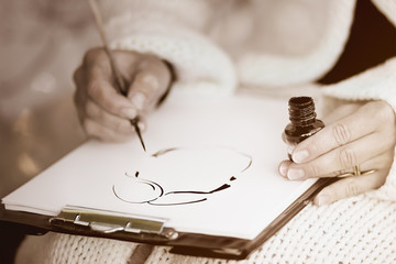 Female's hands drawing a caricature with black ink