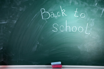 Blank blackboard with colored chalks and eraser.