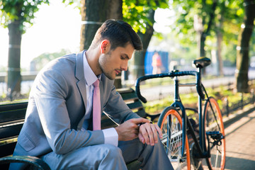 Businessman looking on wrist watch outdoors