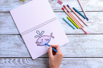 Female hand drawing whale in notebook on wooden table background