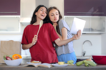 Two young women taking a selfie while cooking in the kitchen